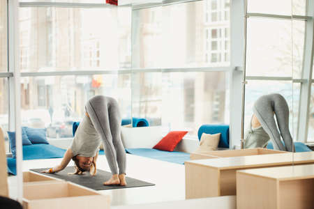 Sporty unrecognizable girl in grey outfit stretching in yoga Dog pose, against big windows overlooking the city, at cute transparent well -lit studio background