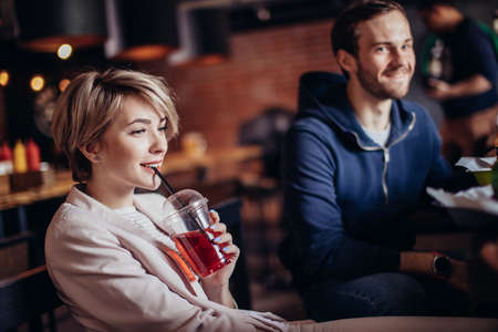Young positive and charming couple enjoying night out at modern loft restaurant, blonde lady sipping non-alcoholic cocktail