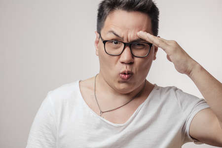 Japanese surprised man wearing spectacles with lips in a tubule holding hand near the temple looking at camera with distrustful expression isolated over white background.