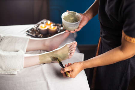 Spa treatment in salon. Beautiful girl getting clay foot mask applying on foot by beautician. Mud therapy. Close up