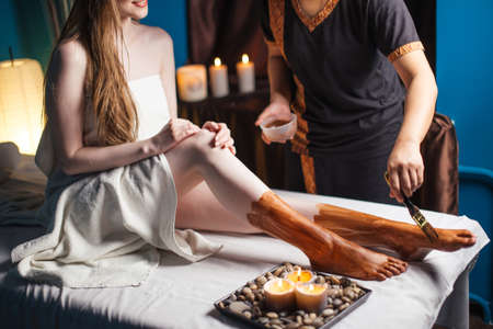 Young woman getting spa treatment in healthcare clinic. Beautiful girl with loose long blonde hair having clay body mask applied by beautician. Mud therapy. Stock Photo
