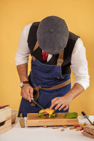 Talented Chef is working on a order of a customer, making delicious burger with green bun on a wooden cutting board on yellow background Banque d'images