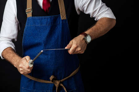Close up mid section shot of unrecognizable chef cook in elegant uniform wearing cap and apron sharpens knife at the restaurant over black background. Small business, Service and Catering Concept