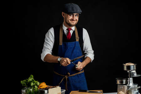 Restaurant Director in classy clothes wearing blue apron, performing masterclass with kitchen utensils knife and sharpen steel tool isolated over black background