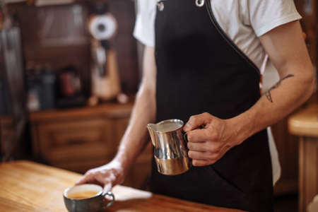 Close up cropped side view image of man pouring milk and preparing fresh cappuccino