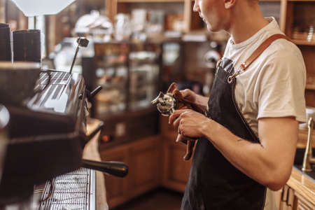 cropped photo of young barista preparing the tamper for work 版權商用圖片