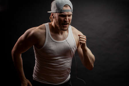 angry runner in grey cap and white singlet isolated on the black background. side view shot