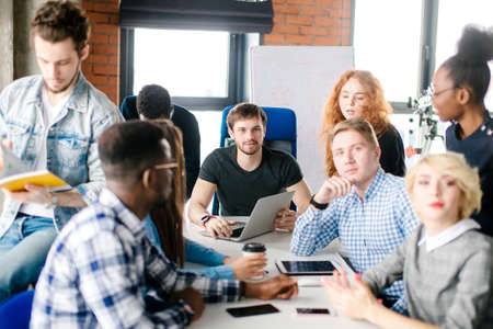 young unexperienced boss cannot force his workers to work. uncontrollable colleagues Stock Photo