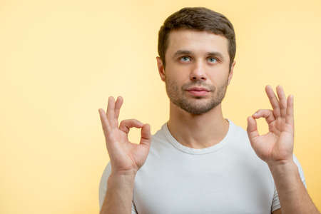 thoughtful guy isstanding in yoga pose and looking up. copyspace. positive thinking concept.