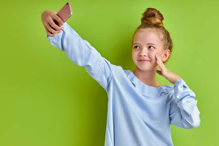sweet positive child girl take selfie on mobile phone, take photo of herself, looking at screen of smartphone, isolated over green background
