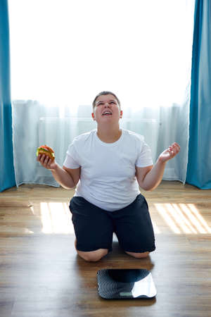 an overweight child is sitting on knees near the scales and scream, thinks wnen he will stop junk food