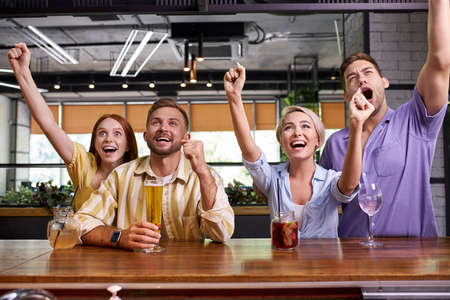group of friends watching soccer in pub, celebrate the winning, laugh and scream. happy