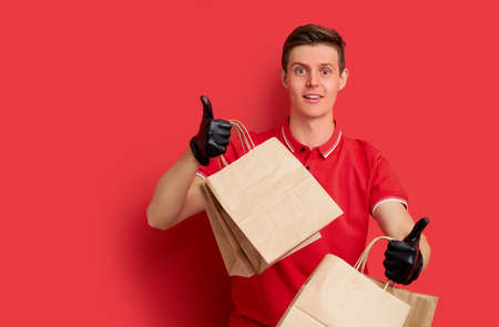 man in red uniform with fast food order isolated on red background, male courier holding paper packet with food for clients, wearing protective gloves, show thumbs up Фото со стока