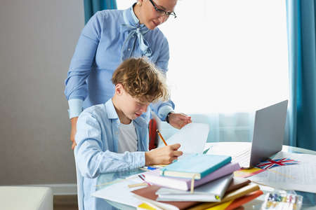 young blonde female tutor came to schoolboy at home, share knowledge, explain, teach all rules he needs for best marks in school Standard-Bild