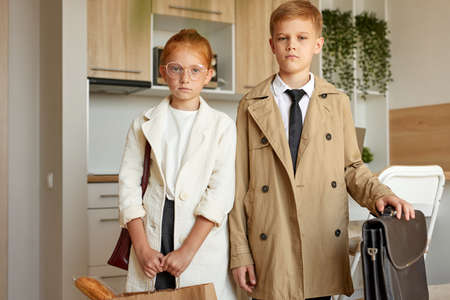 portrait of confident kids couple pretend to be adults, young business boy and girl in formal wear seriously look at camera, indoors