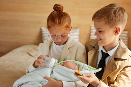 children want to be parents for child, redhead girl and boy sit on bed at home holding baby in hands, love concept