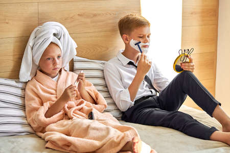 adorable kids couple have happy morning, take care of themselves, boy is shaving beard with shaving foam on face, at home on bed, girl with towel on head saws the nail next to him