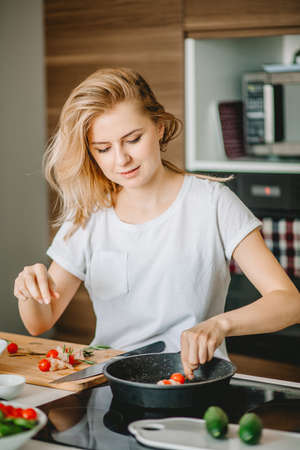 good-looking fair-haired housewife frying tomatoes on the cooker. prepare food according to the recipe