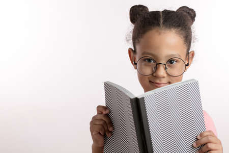 Little smiling girl sitting with a book. Isolated over white. close up portrait. copy space. schoola nd education concept. talented, gifted child. child prodigy