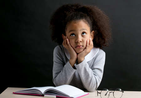 little beautiful girl is trying to learn the poem by heart. dreaming school girl sitting at the table with books and glasses