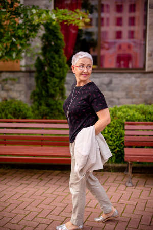 an elderly awesome woman looking back while walking in the city. tourist is going sightseeing