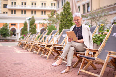 advanced age concept. lovely fair-haired woman looking at the photos from the tablet at the hotel area.side view photo