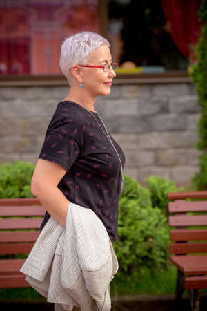 Portrait of a mature woman walking on the street. health care . free time. close up side view photo