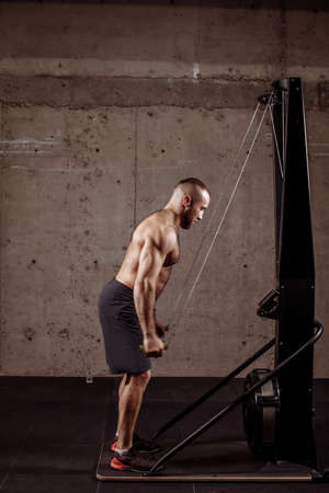 young attractive man with ropes is preparing for the competition in the sport center. full length side view portrait Stockfoto