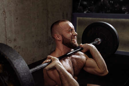 will power concept. muscular strong guy doing deadlift exercise at gym. close up cropped side view shot