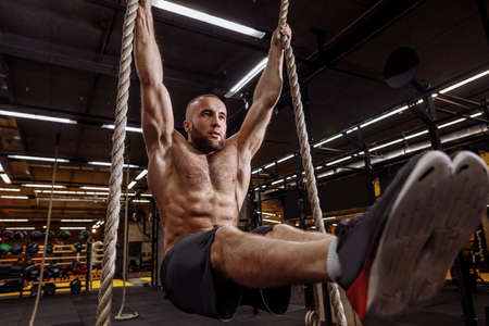 active shirtless sportsman holding ropes. close up low angle view