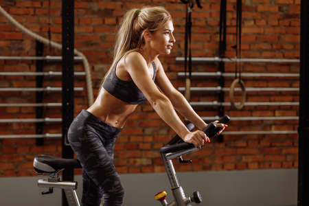 pleasantblond woman is using exercycle in the gym.effective cardiovascular exercise.