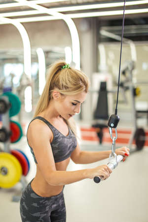 serious fit woman doing exercises on the lat row in the sport center. side view photo. girl develops arms strength