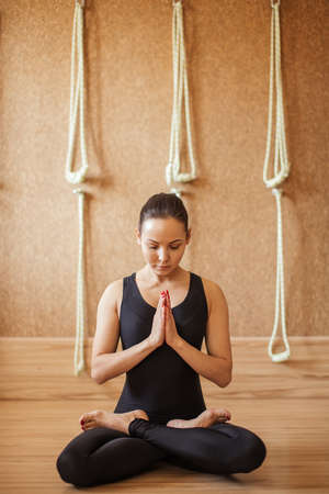 Young pleasant woman witjh joined handssitting in the prayer position.full length photo. fit girl doing padmasana in the sport club