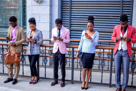 african students playing network games online. entertainment concept.everybody is gazing at mobile phones. stylish people with modern gadgets