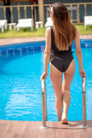attractive girl with long, dark hair in black fashion swimwear is ready to swim in the pool. health, body care, wellness concept