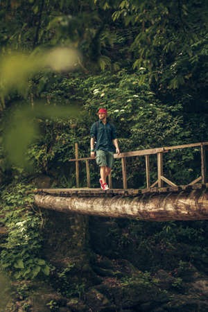 Hiking man wearing red hat and red sneakers walking on wooden footbridge in a deciduous forest at the swedish island. Imagens