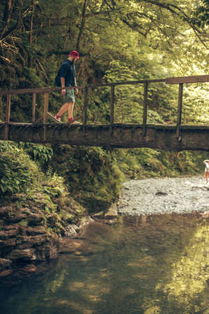 Young caucasian Hiker in red hat and travelling clothes with backpack standing on the wooden old bridge surrounded by lush tropical forest Imagens