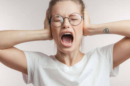 Nervous attractive blonde female in despair after a big collapse in her life, keeps hands on temples, dressed casually, opens her mouth screaming, close up shot, isolated over white background.