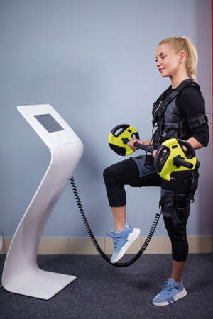 pleasant blonde wearing EMS costume working out with barbell indoors. bodybuilding concept