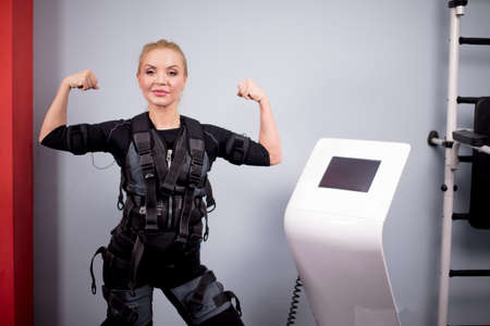 cheerful fair-haired girl is demonstrating her strong arms to the camera in the sport club.health care and bodybuilding concept