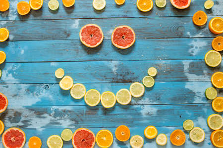 Citrus fruits creative frame, making smile of oranges, limes and lemons. Over wooden table background with copy space Stock fotó