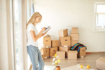 frustrated woman standing with book near cardboard boxes in new house near window