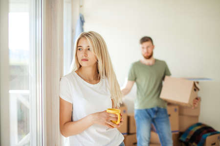 girl dreams near window while her husband does all work. move in home, resettlement concept