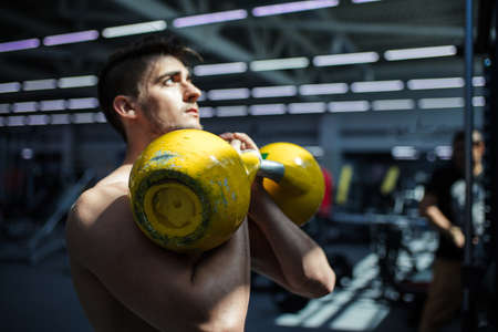 Handsome bodybuilder pumping up muscular body, doing exercises in gym, fitness concept, sport concept Imagens