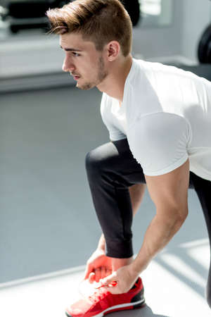 Handsome caucasian sportsman in white t-shirt ties his red sneakers preparing for exercise at gym Standard-Bild