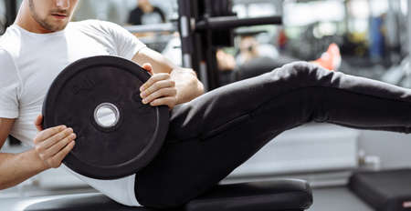Muscular guy in white t-shirt doing sit ups at gym. Young athlete doing stomach workout in modern fitness studio.