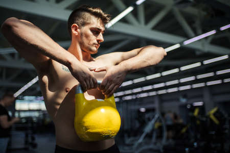 Caucasian handsome sportive man having functional fitness training with kettlebell in sport gym