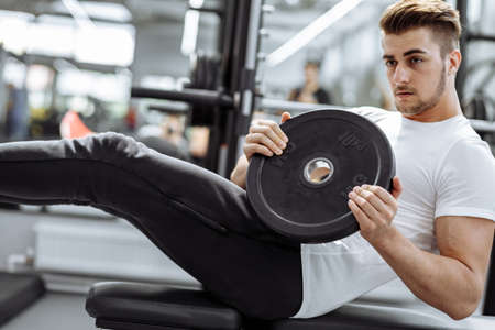 Handsome fit man in sportwear doing crunches at gym. Handsome People, Healthy lifestyle, Sport Indoors