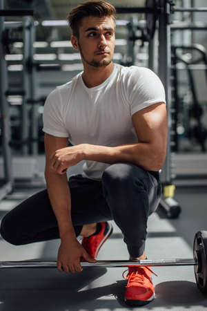 Attractive young male bodybuilder at indoor workout in well-equipped gym, prepare to lift weight