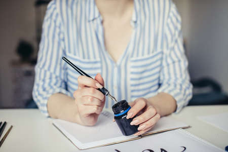 Close up of Female hand dipping calligraphy pen into inkwell
